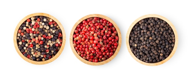 白い背景で隔離の木製のボウルにホット、赤、黒、白の唐辛子の混合物。上面図