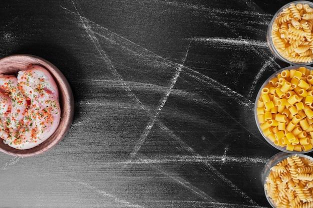 Смешанные макаронные изделия в металлических чашках с сырым куриным мясом в сторону.