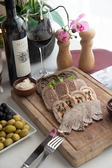 Mixed pate plate on wooden board walnuts vegetables side view