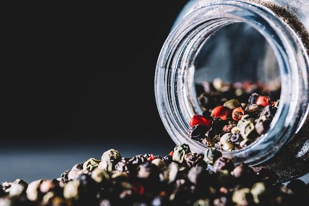 Mixed peppercorns spilling from a glass jar