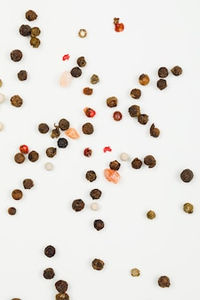 Mixed peppercorns on white. flat lay. vertical.