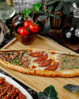 Mixed pide filled with sausage, cheese and meat