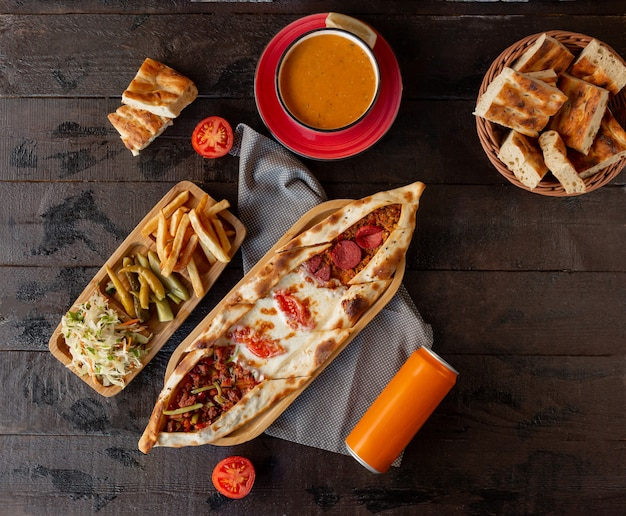 Mixed pide with pepperoni, cheese, minced meat served with pickles and tomato soup