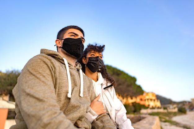 코로나 바이러스 전염병에 대한 검은 보호 마스크를 쓰고 일몰을보고 바다 리조트에서 야외에 앉아있는 그녀의 백인 남자 친구를 껴안은 혼혈 아프리카 계 미국인 소녀. 새로운 일반 휴가 여행