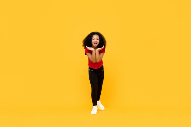 Mixed race afro girl in surprised excited gesture with hands open isolated on yellow wall