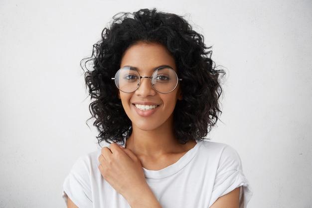 Donna di college nero di razza mista con acconciatura riccia che sorride ampiamente vestita in camicetta bianca, guardando fresca e giovane, indossando occhiali alla moda. emozioni e sentimenti umani positivi