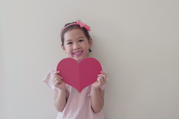 Mixed race child holding big red heart, heart health, donation, happy volunteer charity, social responsibility,world heart day, world health day,world mental health day, wellbeing, hope concept