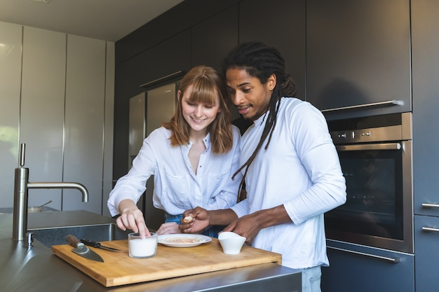 Mixed race couple cooking together in the kitchen.