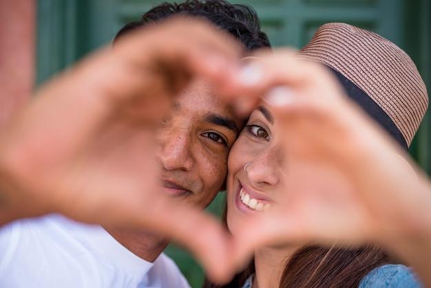 混合レースのカップルは、カメラを見て、手で囲炉裏サインを行います-若い男性と女性との愛と関係の概念-一緒にボーイフレンドのガールフレンド-友情千年紀の男の子と女の子