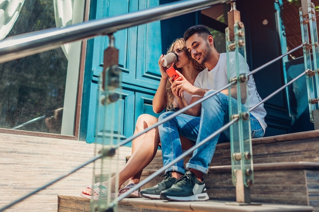 Mixed race couple in love chilling on stairs in city. arab man and white woman drinking coffee and using smartphone outdoors