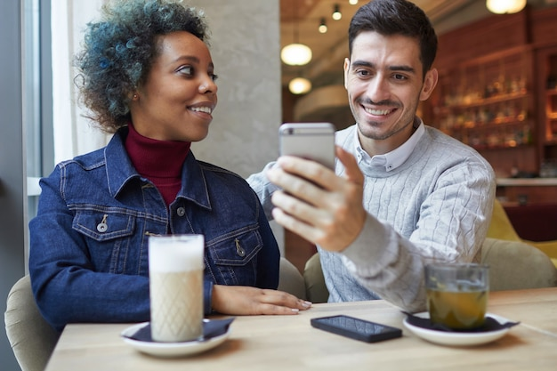 Mixed race couple sitting in cafe and sharing new app using smartphone