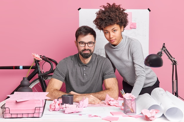 Коллеги из смешанной расы создают архитектурные проекты, рисуют чертежи, создают эскизы на рабочем месте со скомканными бумагами на столе, обсуждают важные вопросы, улучшают навыки совместной работы. два опытных архитектора