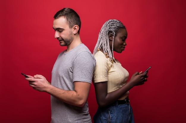 Смешанная раса милая женщина и красивый мужчина стоят спиной к спине и пишут смс