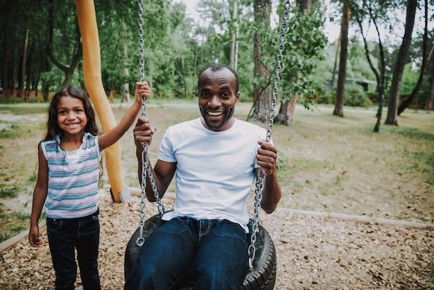 Mixed race daughter swinging dad amusement park.