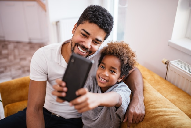 Mixed-race father and daughter taking a selfie at home.