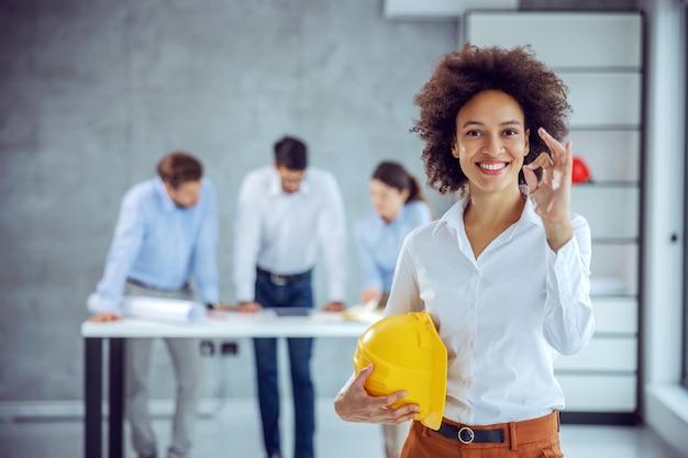 Женский архитектор смешанной расы, стоящий в офисе, держа шлем в руках и показывая хороший жест. там работают ее коллеги.