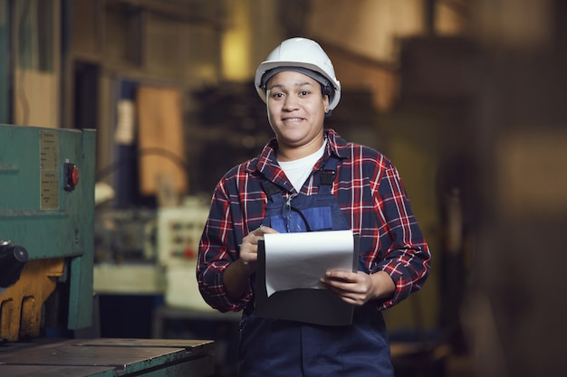 Mixed-race female worker holding clipboard