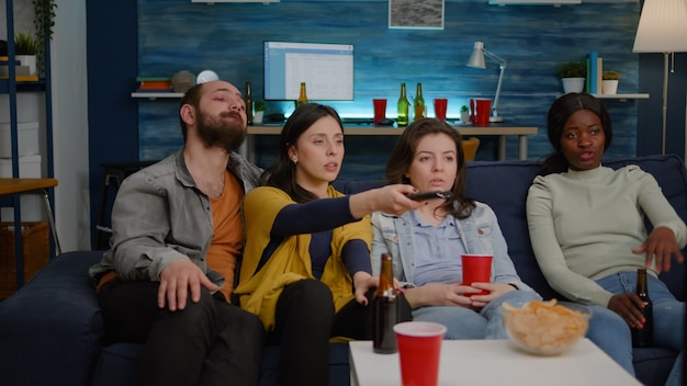 Mixed race friends changing channels until find comedy movie on television