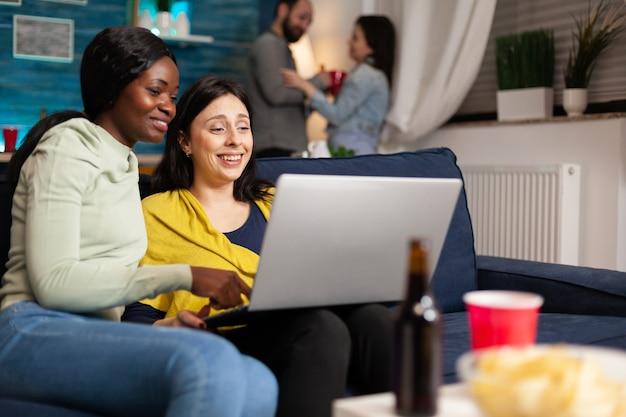 혼혈 친구들은 거실에 있는 소파에 앉아 노트북으로 재미있는 비디오 시리즈를 보면서 이야기합니다. 백그라운드에서 여자와 남자 재미 파티 동안 함께 시간을 즐기는 맥주를 마시는.