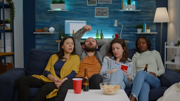 Mixed race friends watching funny video on television sitting on sofa late at night in living room d...