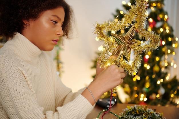 金色の見掛け倒しでクリスマスツリーのトッパーを飾ることに集中した混血の少女