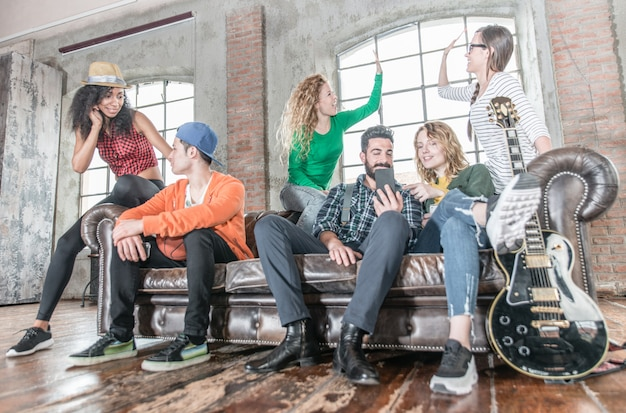 Группа смешанной расы развлекается на диване в мансарде