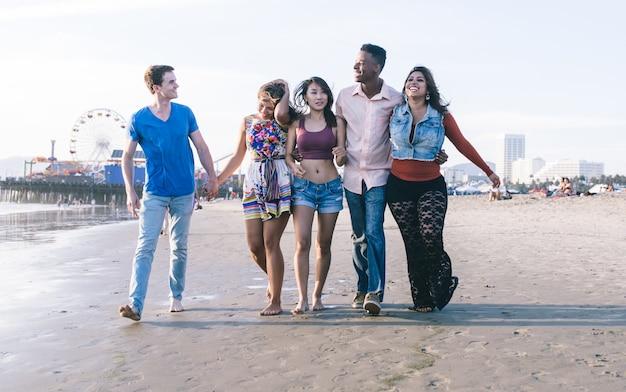 Группа друзей смешанной расы, прогуливаясь по пляжу санта-моники