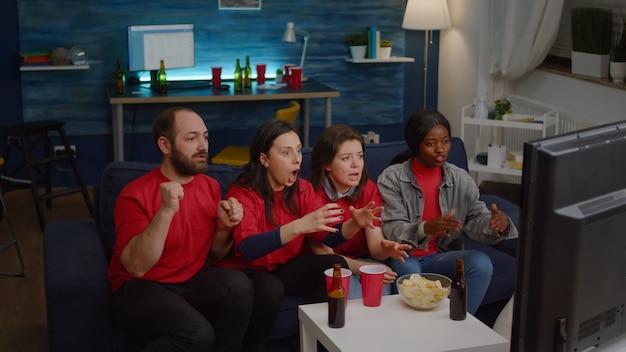 Группа людей смешанной расы, смотрящая на футбольный матч по телевизору, приветствуя спортивную команду