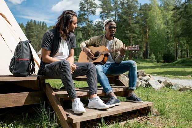 Парень смешанной расы сидит на крыльце палатки и слушает, как черный друг играет на гитаре