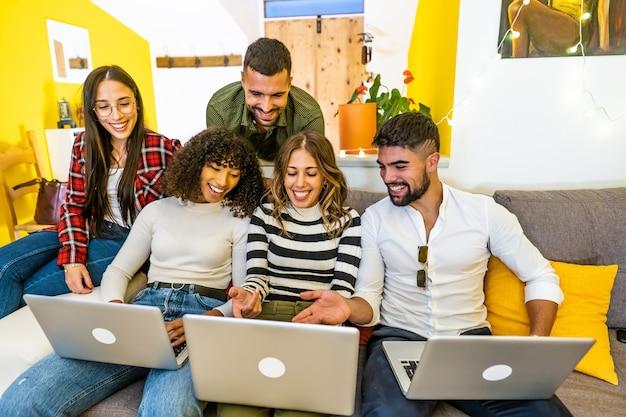 自宅のソファで3台のラップトップを使用する混血の幸せな友達グループ-コンピューターを見ているソーシャルネットワークと一緒に楽しんでいる若者-