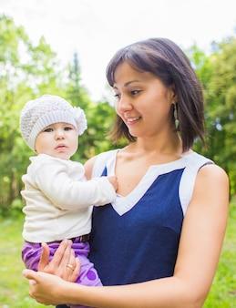 女の赤ちゃんの屋外の肖像画との混血の幸せな母。