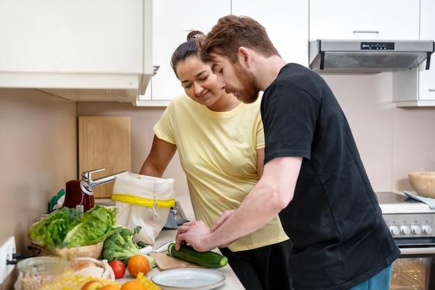 ビーガン料理を準備する混血の幸せな若いカップル。魅力的な白人男性と混血の女性がキッチンでビーガンの食事を準備しています。ビーガン自然料理。快適な調理。実生活の概念
