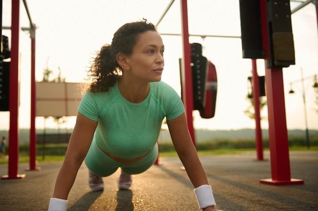 スポーツウェアを着た混血のヒスパニック系女性は、屋外で運動し、スポーツグラウンドで腕立て伏せを行い、暖かい晴れた夏の日に体重トレーニングを行います。ボディケア、フィットネス、アクティブなライフスタイルのコンセプト
