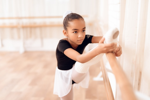 Mixed race kid is stretching near ballet bar.
