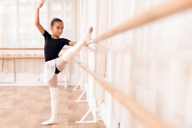Mixed race kid is stretching near ballet barre.