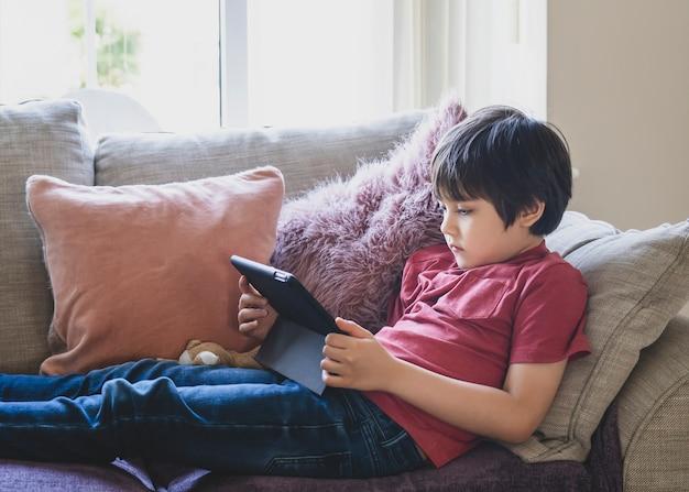 タブレットで漫画を見てソファーに座っている、またはタッチパッドでゲームをプレイしている混血の子供。