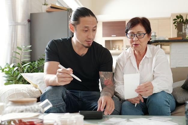 가계를 관리하고 청구서를 지불하는 성숙한 어머니를 돕는 혼혈 남자