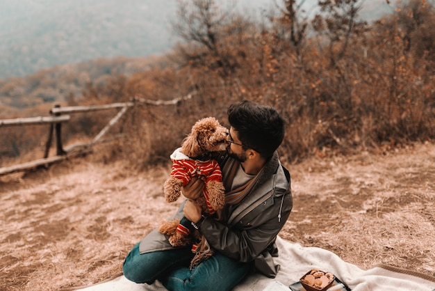 Mixed race man in raincoat hugging and cuddling his poodle while sitting on blanket in nature at autumn.