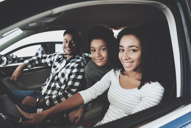 Mixed race marriage and kid family buying car.