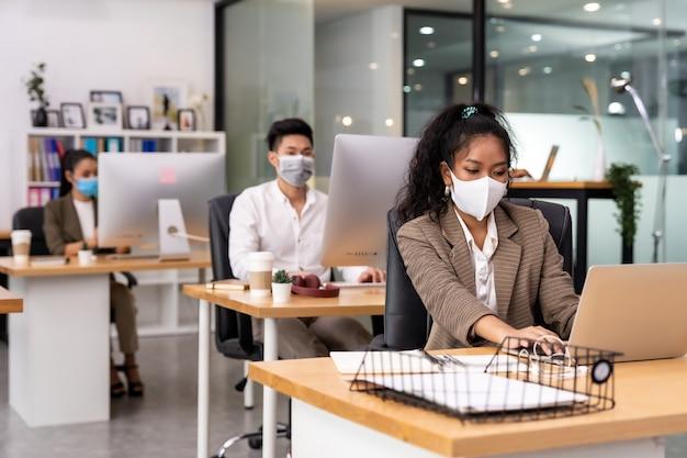 アフリカの黒人とアジア人のビジネスウーマンの混血は、コロナウイルスcovid-19の拡散を防ぐために、ビジネスチームの人々のグループとの社会的距離を持つ新しい通常のオフィスで働くフェイスマスクを着用します