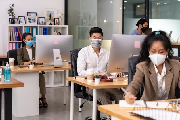 Смешанная раса африканских чернокожих и азиатских бизнес-леди носит маску для лица, работая в новом нормальном офисе.