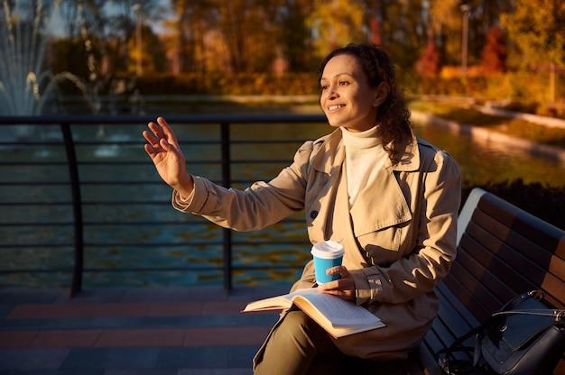 베이지색 옷을 입은 혼혈 미녀가 공원 벤치에 앉아 커피와 핸드북을 들고 노란색 단풍이 반사된 아름다운 호수의 배경을 바라보며 인사를 하고 있다