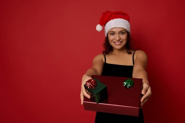 아름다운 이빨 미소를 지닌 산타 모자를 쓴 혼혈 미녀는 크리스마스 선물을 뻗은 손에 들고 빨간색 배경 위에 격리된 카메라를 보며 광고를 위한 복사 공간을 보여줍니다.