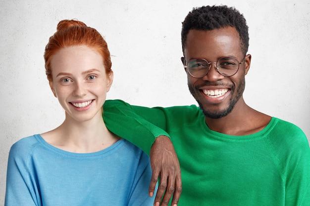 Concetto di relazioni di razza mista. l'uomo e la donna in bianco e nero felici delihghted indossano maglioni luminosi, posano insieme contro il bianco