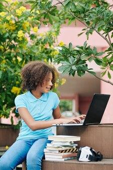 Школьница смешанной расы сидит в кампусе со стопкой книг и очками виртуальной реальности и работает на ноутбуке