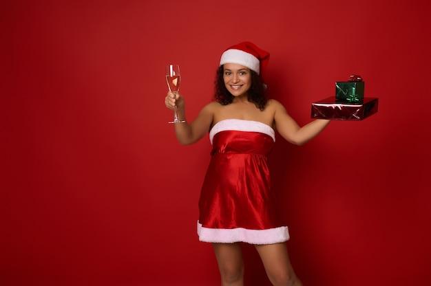 산타 의상을 입은 혼혈 섹시한 예쁜 여성은 반짝이는 빨간색 녹색 선물 종이로 싸인 크리스마스 선물 상자를 들고 샴페인과 플루트를 들고 빨간색 배경에 포즈를 취하고 카메라를 바라보는 귀여운 미소