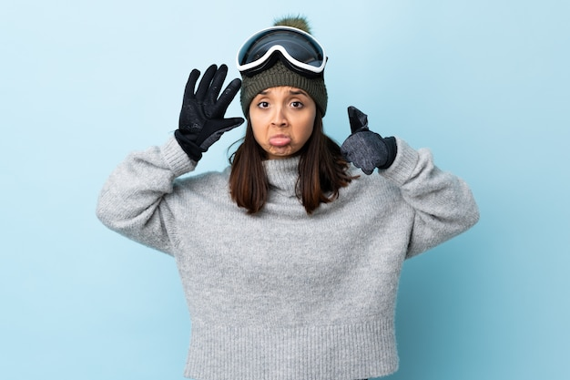 Mixed race skier girl with snowboarding glasses over blue wall counting six with fingers