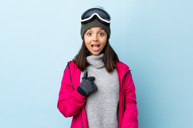 Mixed race skier girl with snowboarding glasses over blue wall with surprised facial expression