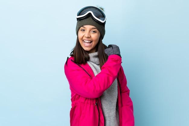 Mixed race skier girl with snowboarding glasses over isolated blue background celebrating a victory