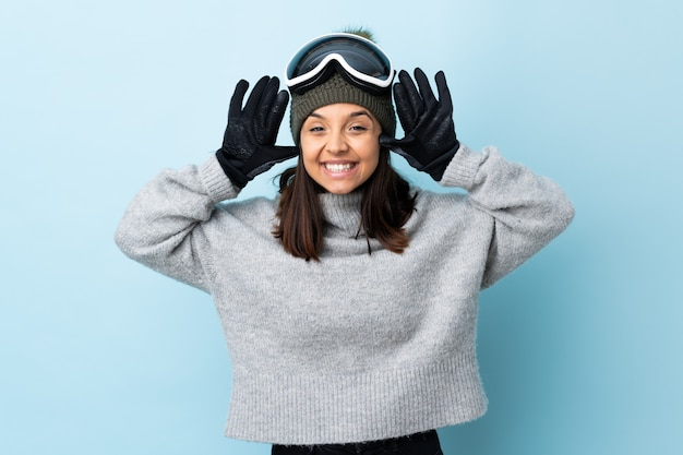 Mixed race skier girl with snowboarding glasses over isolated blue background counting ten with fingers